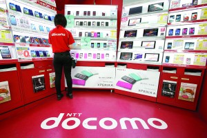An employee stands by a display of NTT DoCoMo Inc. mobile devices and tablet computers alongside Sony Corp. Xperia products at an electronics store in Tokyo, Japan, on Tuesday, Sept. 10, 2013. Apple Inc. is close to securing deals with China Mobile Ltd. and Japan's NTT DoCoMo Inc. to sell iPhones in Asia's biggest markets. Photographer: Kiyoshi Ota/Bloomberg via Getty Images